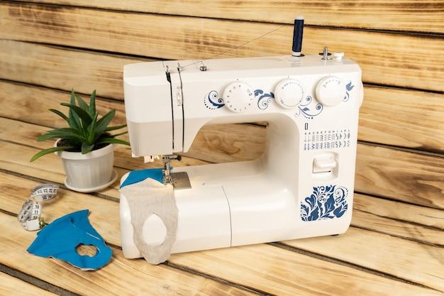 Een witte naaimachine waarop medische maskers voor coronavirus zijn genaaid
