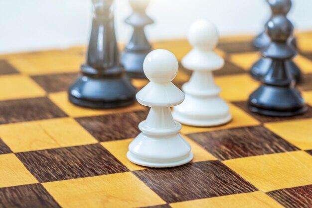 Een witte pion op schaakbord onder andere schaakstukken.