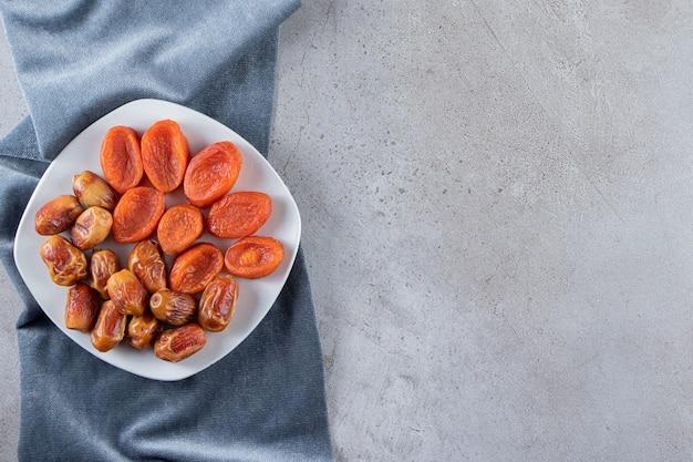 Een witte plaat met gedroogde abrikozenvruchten en ontpitte dadels op een stenen tafel.