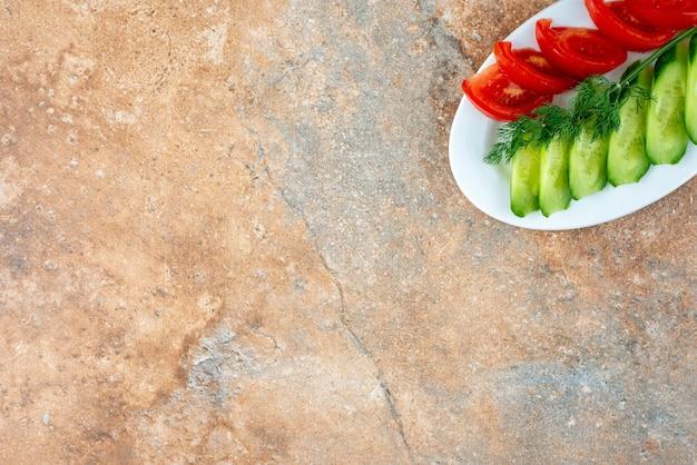 Een witte plaat met gesneden komkommer en tomaat op marmeren tafel.