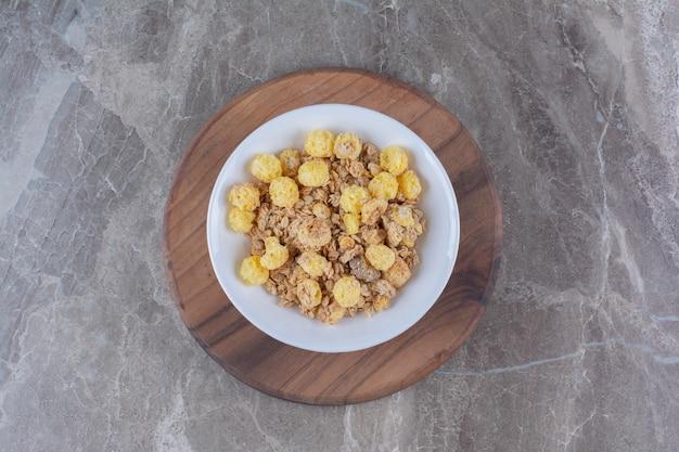 Een witte plaat met gezonde cornflakes op een houten rond bord.