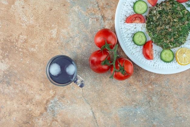 Een witte plaat met groenten en een kopje sap.