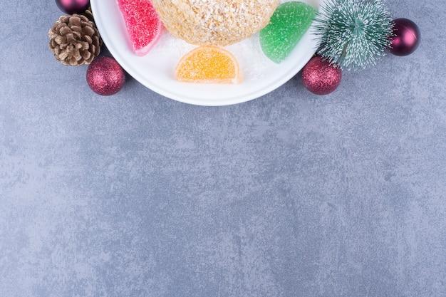 Een witte plaat met koekje en suikerachtig geleisuikergoed