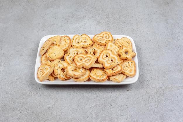 Een witte plaat met koekjes erop op marmeren achtergrond.