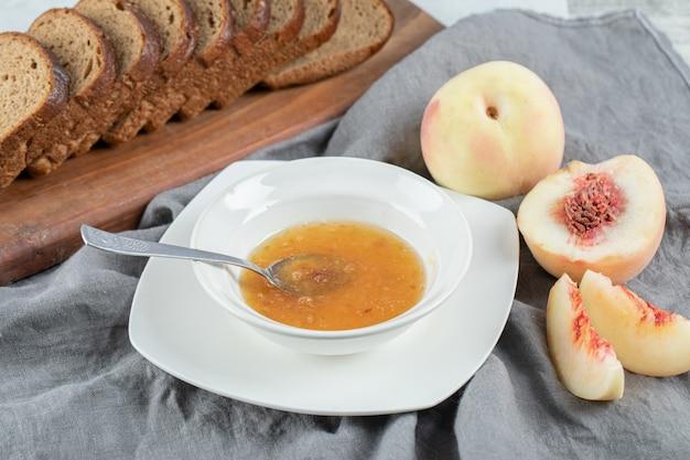 Een witte plaat met perzikjam en sneetjes bruin brood.