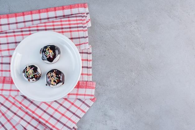 Een witte plaat met smakelijke geglazuurde koekjes op stenen tafel.