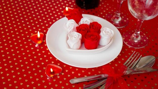 Een witte plaat met wijn, een mes en vork op een felrode achtergrond. rode en witte rozen decoratie. tafelschikking voor valentijnsdag