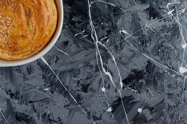 Een witte plaat van azerbeidzjaanse gohal op een marmeren tafel.