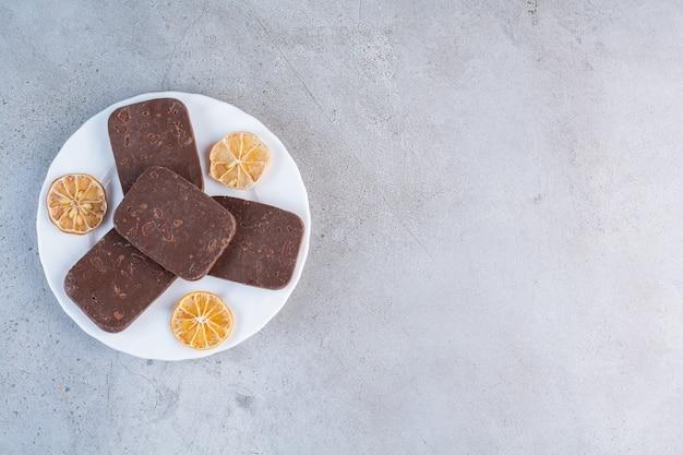 Een witte plaat van chocoladekoekjes met gesneden gedroogde citroen op grijze achtergrond.