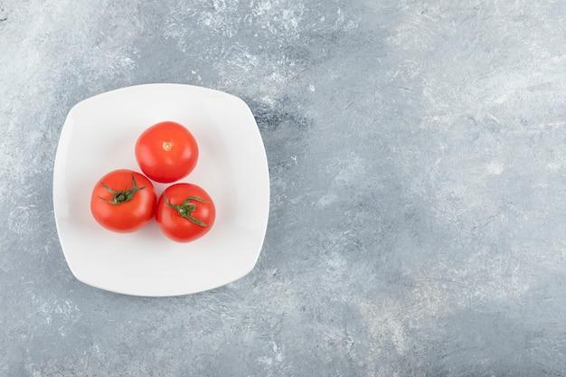 Een witte plaat van drie verse rode tomaten op een stenen achtergrond.