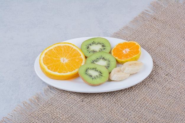 Een witte plaat van gesneden fruit op zak. hoge kwaliteit foto