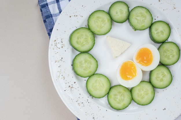 Een witte plaat van gesneden komkommer en gekookt ei.