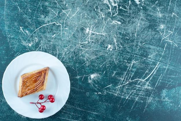 Een witte plaat van heerlijk zoet gebak op een blauwe achtergrond. hoge kwaliteit foto