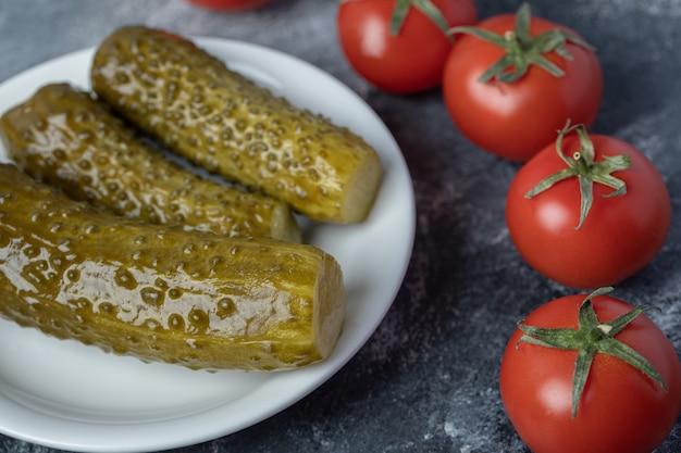 Een witte plaat van ingelegde komkommers met tomaten.