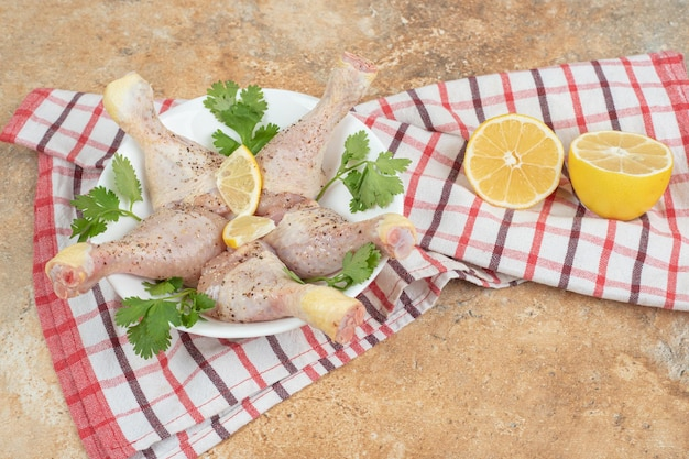 Een witte plaat van kippenpoten met gesneden citroen