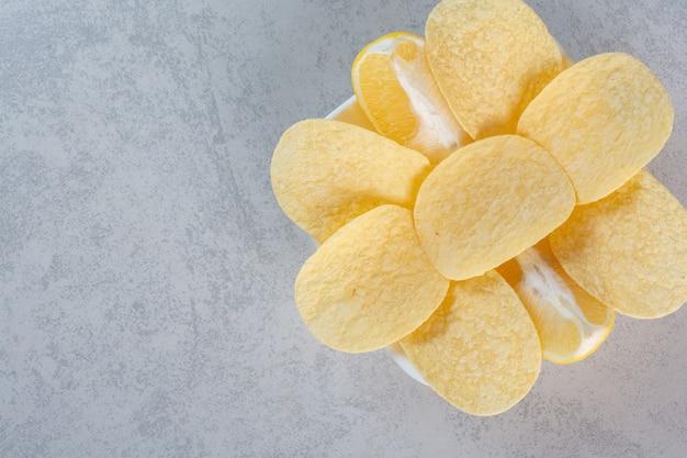 Een witte plaat van knapperige chips op grijs.