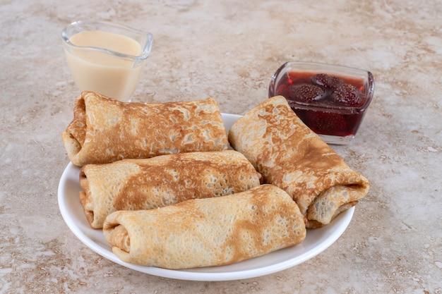 Een witte plaat van lekkere pannenkoeken en aardbeienjam