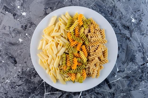 Een witte plaat van rauwe droge multi gekleurde fusilli pasta met penne macaroni. Gratis Foto