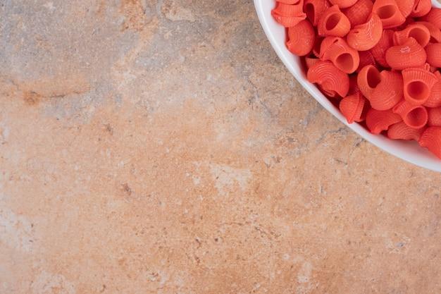 Een witte plaat van rode ongekookte macaroni op marmeren achtergrond. hoge kwaliteit foto