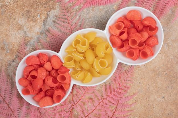 Een witte plaat van rode ongekookte macaroni op marmeren ruimte.