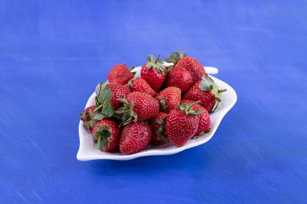 Een witte plaat vol aardbeien op blauw oppervlak