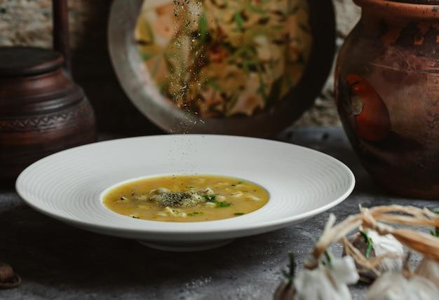Een witte plaat vol bouillon soep met vlees stukken binnen.
