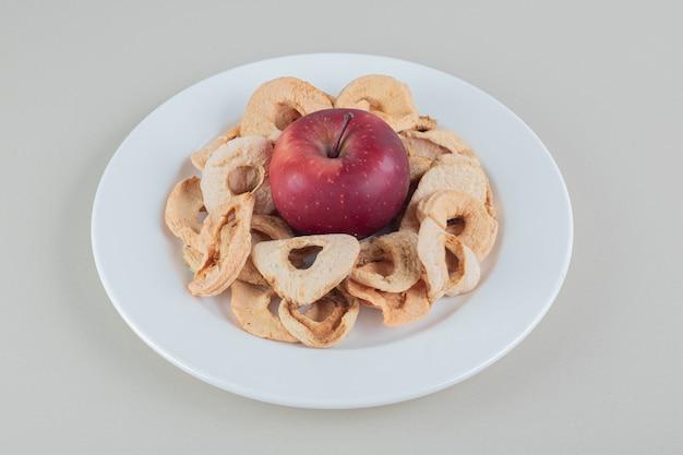Een witte plaat vol gedroogd appelfruit met een hele appel.