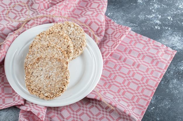 Een witte plaat vol gepofte rijstbrood op een tafelkleed.