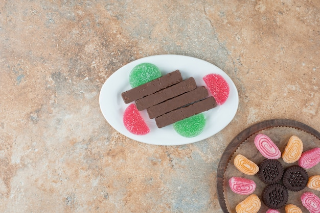 Een witte plaat vol koekjes en marmelade op marmeren achtergrond