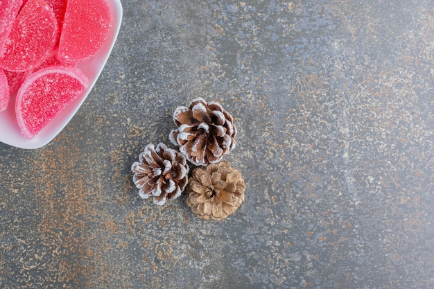 Een witte plaat vol met geleisuikergoed van rood fruit en dennenappels. hoge kwaliteit foto