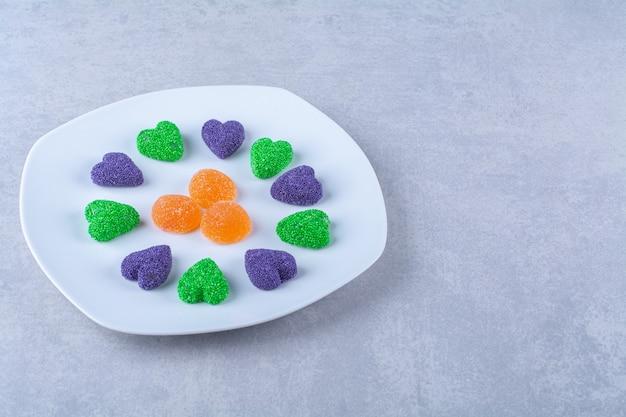 Een witte plaat vol suikerachtige gelei snoepjes op grijze tafel.