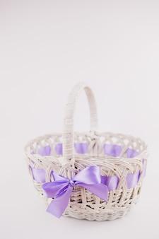 Een witte rieten mand met paars lint