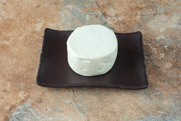 Een witte ronde kaas op een donkere plaat op marmeren tafel.