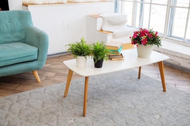 Een witte salontafel staat bij een raam met potplanten en boeken erop in een lichte woonkamer