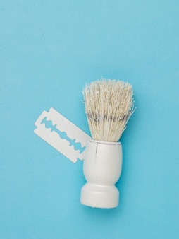 Een witte scheerkwast en een wit mes op een blauwe ondergrond