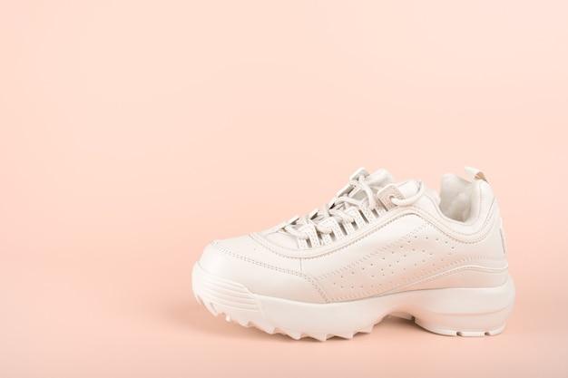 Een witte sneaker geïsoleerd op pastel achtergrond schone nieuwe trendy sneaker