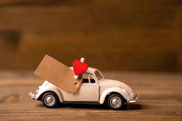 Een witte speelgoedauto met een hart met een stuk papier voor notities op een houten achtergrond