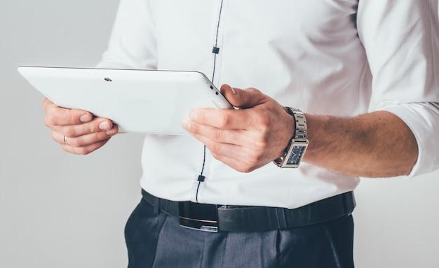Een witte tablet is in handen van een man. hij staat in een wit overhemd en zwarte broek en leest informatie uit de gadget