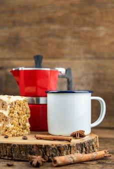 Een witte tinnen kop warme koffie met italiaanse koffiepot (moka) en cake op houten tafel.