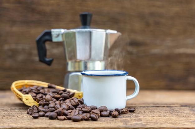 Een witte tinnen kop warme koffie met italiaanse koffiepot (moka) en koffiebonen op houten tafel.