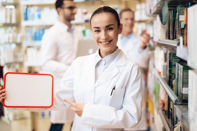 Een witte vrouwelijke apotheker houdt een map met papieren vast.