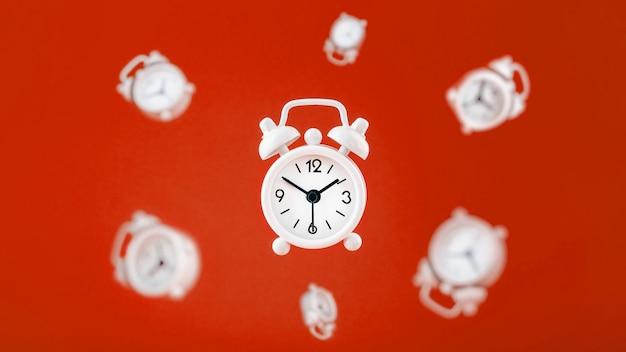 Een witte wekker in levitatie in het midden, geïsoleerd op een rode achtergrond met een omgeving van zwevende wekkers op de achtergrond.