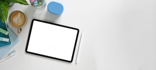 Een witte werkruimte wordt omgeven door een computerlaptop, hoofdtelefoon en accessoires.