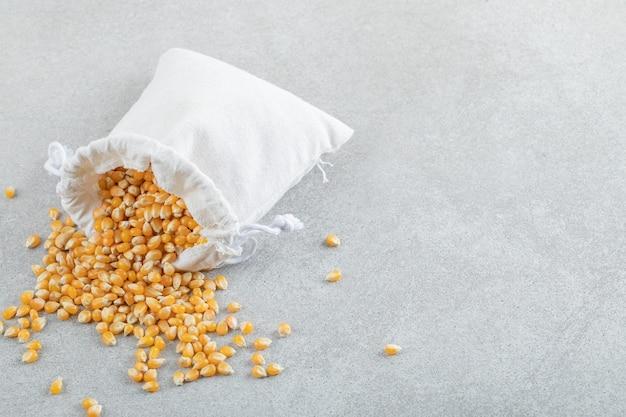 Een witte zak vol maïskorrels op een grijze achtergrond.