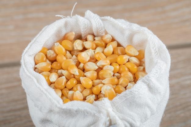 Een witte zak vol maïskorrels op een grijze ondergrond.