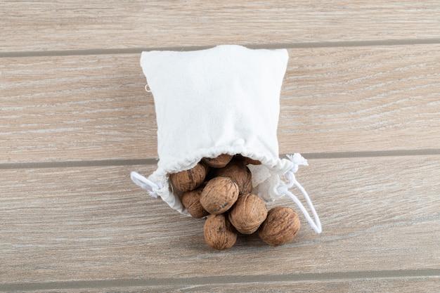 Een witte zak vol walnoten op een houten tafel.