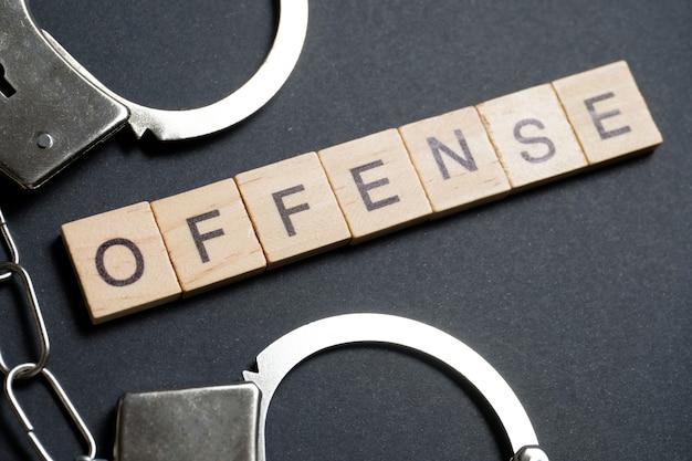 Een woord gemaakt van houten letters is een overtreding. metalen handboeien op een zwarte.