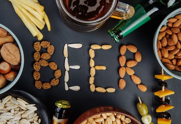 Een woordbier gemaakt van gezouten krokante noten, zonnebloempitten en broodkoekjes, zoute snacks met kaaskaasflessen bier en een mok bier op zwart bovenaanzicht