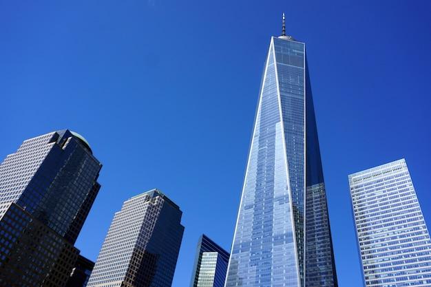 Eén world trade center in de stad vs van new york. uitzicht vanaf het 9.11 gedenkteken op een zonnige dag.