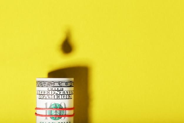 Een worp van amerikaanse biljetten met de schaduw van een olievat en een druppel olie op een gele achtergrond